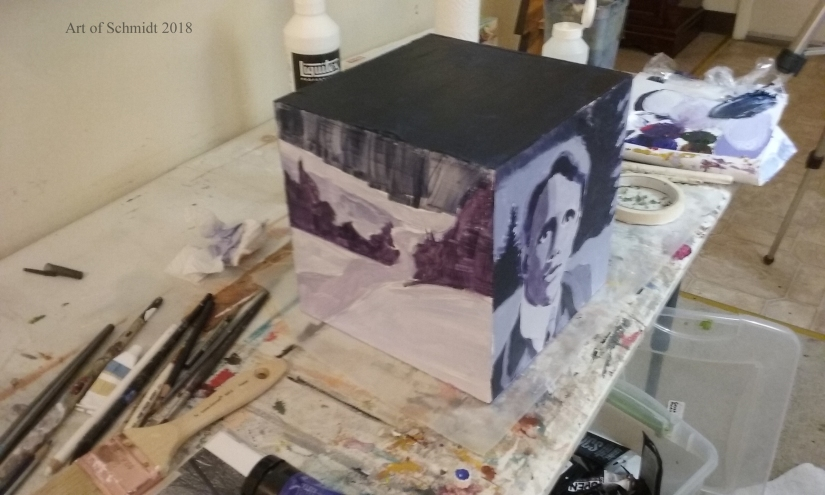Three dimensional cube with portrait and landscape painting.